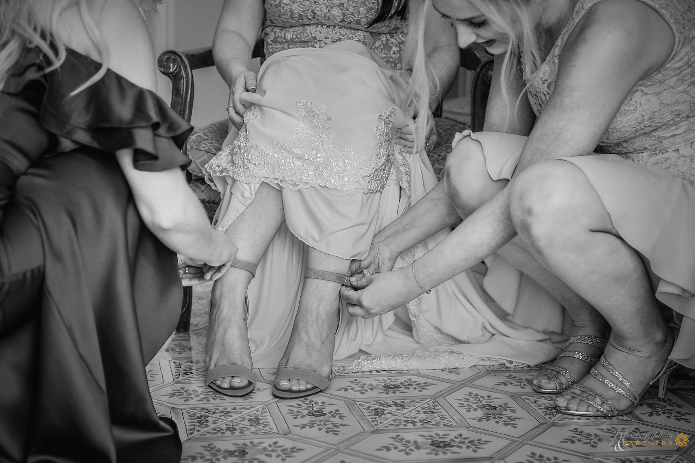 Bridesmaids help the bride put on the shoes