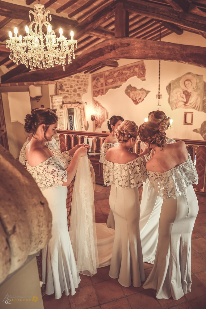 The bridesmaids help the bride with the wedding dress...