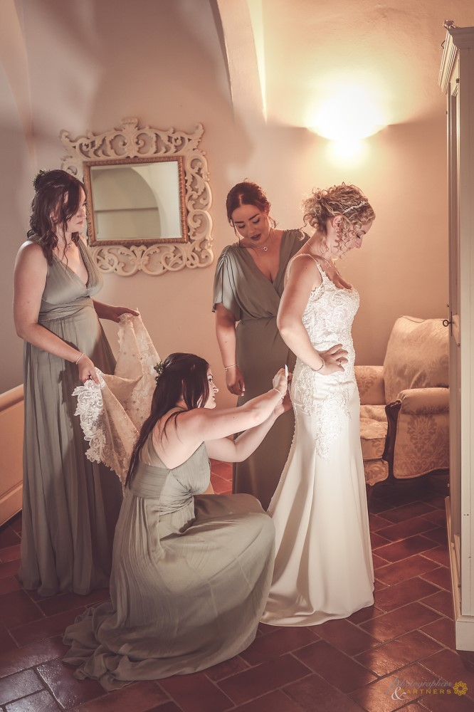 The bridesmaids help the bride with the dress.